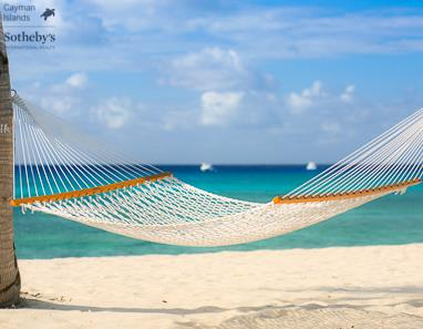 Hammock swinging between two palm trees on Seven Mile Beach, Grand Cayman