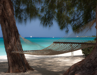 Hammock between two trees on Seven Mile Beach at White in front of Caribbean Sea