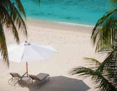Sunbed on Seven Mile Beach shaded by palm trees overlooking Caribbean Sea