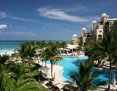 View across swimming pool towards Seven Mile Beach and the Caribbean Sea at The Ritz-Carlton Grand Cayman